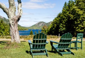 Green Adirondack Chairs Overlooking Lake