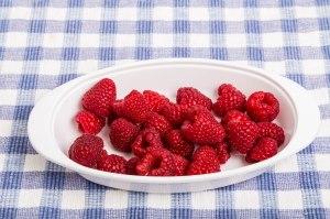 White Bowl of Raspberries on Blue Plaid Towel
