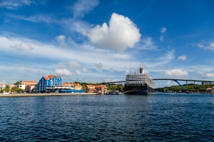 Cruise ship docked in the colorful port of Curacao on blue sea